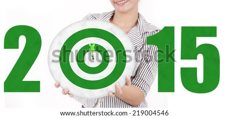 Close up of woman showing a green dartboard shaped number 2015 - stock photo