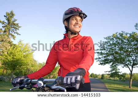 Close-up of woman standing next to bicycle and smiling. Wearing sports gear and helmet. Horizontally framed shot. - stock photo