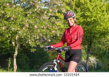 Close-up of woman standing next to bicycle in park and smiling. Wearing sports gear and helmet. Horizontally framed shot. - stock photo