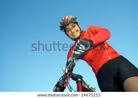 Close-up of woman standing next to bicycle, looking down and smiling. Wearing sports gear and helmet. Horizontally framed shot. - stock photo