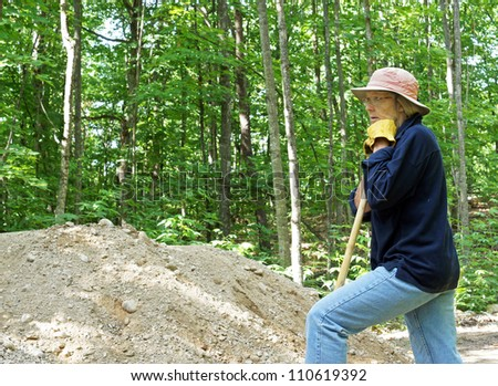 Close up of woman taking a break from moving gravel while at the cottage