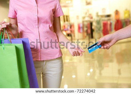 Close-up of woman taking plastic card from male hand in the mall - stock photo