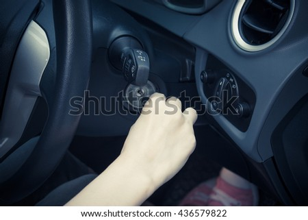 Close up of woman turning on his car. - stock photo