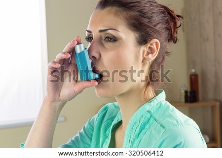 Close-up of woman using asthma inhaler at home - stock photo