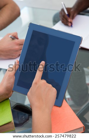 Close up of woman using digital tablet in meeting - stock photo