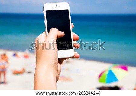 Close up of woman using mobile smart phone,sending massages on the beachfront.having sunbath.Phone with black screen,texting,video calls,sea front,holidays work,using internet - stock photo