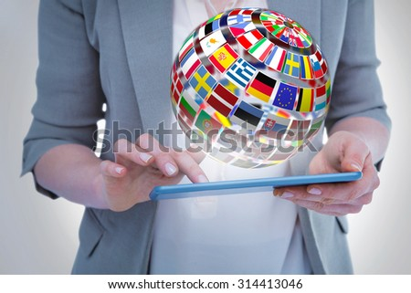 Close up of woman using tablet against sphere made of flags