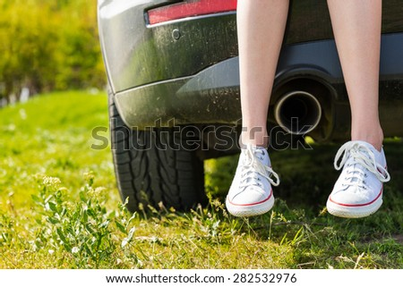 Close Up of Woman Wearing Sneakers Sitting with Crossed Ankles on Rear Tailgate of Vehicle with View of Exhaust Pipe