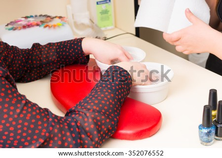 Close Up of Woman with Hands Soaking in Small Bowls of Warm Soapy Water with Manicurist Tearing Piece of Paper Towel for Drying in Background During Spa Manicure - stock photo