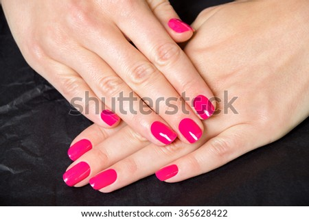 Close Up of Woman with Manicure in Bright Pink - Detail of Female Hands Folded and Wearing Bright Pink Nail Polish on Dark Background