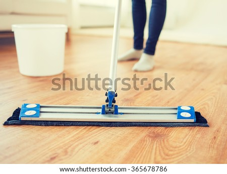 close up of woman with mop cleaning floor at home - stock photo