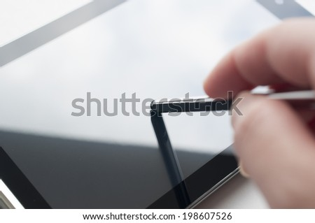 Close-up of woman working with stylus on digital tablet pc, focus on pen head  - stock photo