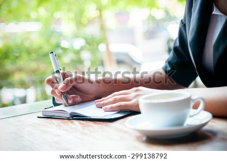 close up of woman writing journal and cup of coffee  - stock photo