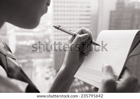 Close up of woman writing something on paper - stock photo