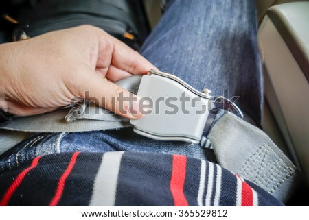 Close-up of women fastening security belt in airplane. selective focus. - stock photo