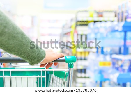 Close up of women hand pushing shopping trolley in supermarket, focus on hand - stock photo