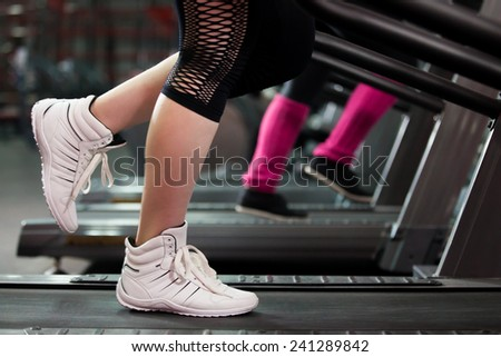 Close-up of women legs in sneakers on treadmill in gym - stock photo