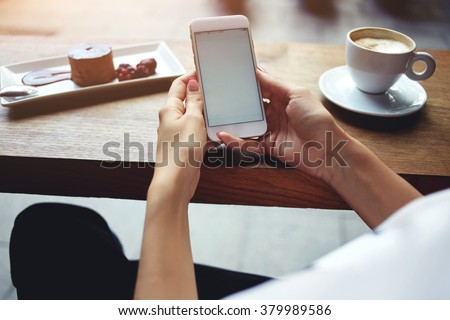 Close up of women's hands holding mobile phone with blank copy space screen for your advertising text message or promotional content, female reading news on cell telephone during rest in coffee shop  - stock photo