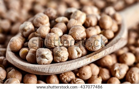 Close up of wood spoon full of chick peas beans. Chick-pea background. Nut is a main ingredient of hummus and many other vegan dishes. - stock photo