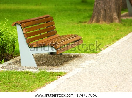 Close-up of wooden bench in park. Peaceful place with green grass. - stock photo