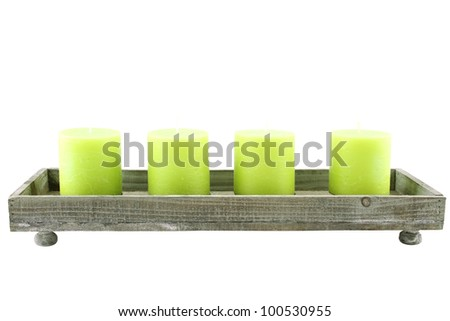 Close up of wooden candlesticks with a few green candles. Isolated on white background