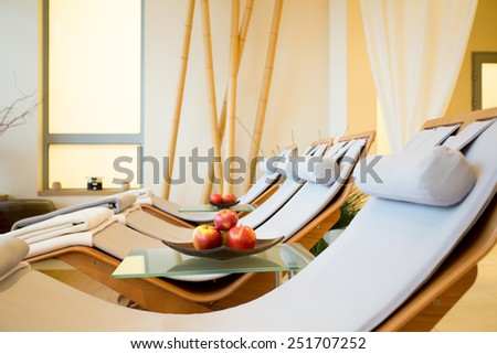 Close-up of wooden fancy loungers in restful room - stock photo