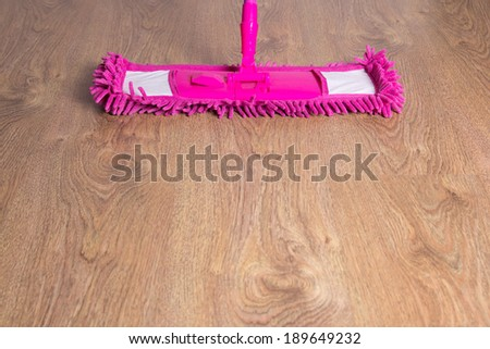 close up of wooden floor with pink cleaning mop - stock photo