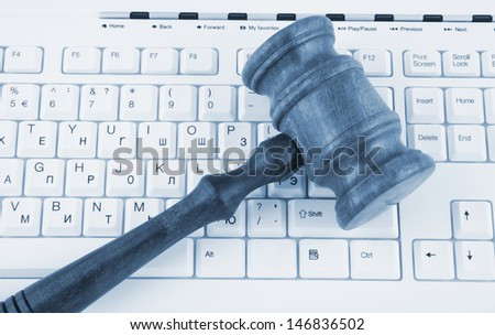 Close up of wooden gavel on white computer keyboard  - stock photo