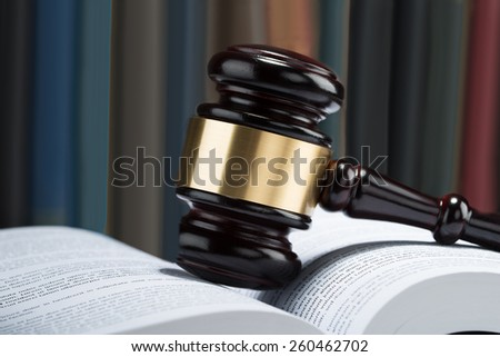 Close-up Of Wooden Gavel With Stack Of Book On Table - stock photo