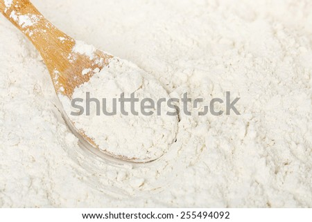 close up of wooden ladle in flour - stock photo
