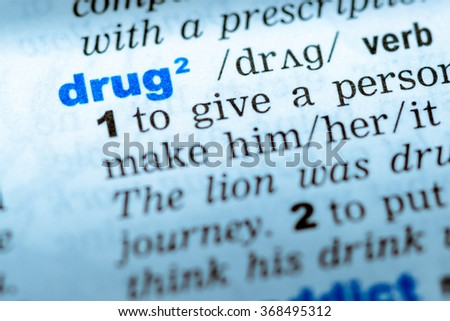 Close-up of word in English dictionary. Drug, definition and transcription