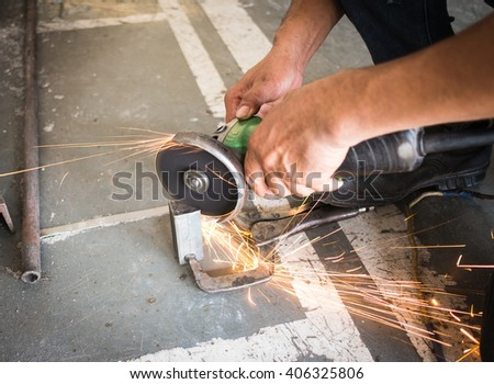 Close-up of worker cutting metal with grinder. Sparks while grinding iron. Low depth of focus