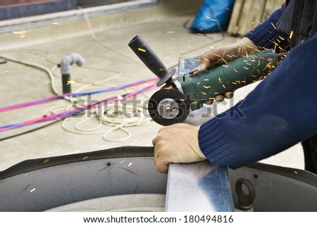 Close up of worker cutting steel or aluminum plate with electrical wheel grinder  - stock photo
