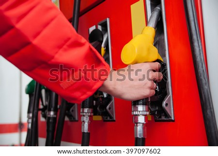 Close Up Of Worker Hand Taking Gun Tank To Refuel Customers Car With Petrol - stock photo