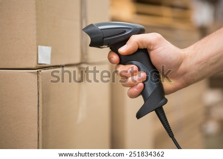 Close up of worker holding scanner in the warehouse - stock photo