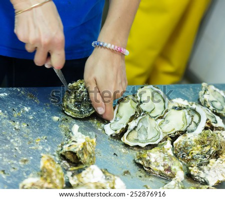 Close-up of worker opening oysters at oyster farm or restaurant - stock photo