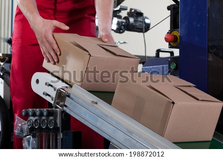 Close-up of worker putting a box on conveyor belt for shipping - stock photo