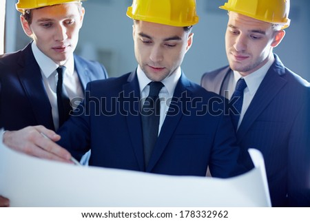 Close-up of workers looking at blue print and planning  - stock photo