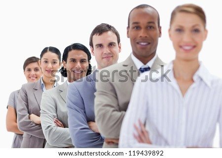 Close-up of workmates dressed in suits crossing their arms in a single line with focus on the last two people - stock photo