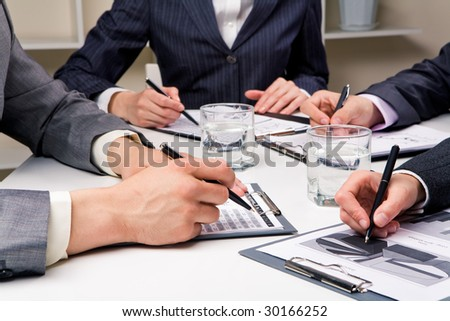 Close-up of workteam reading documents at business meeting