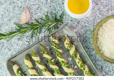 Close up of wrapped asparagus on a baking tray and ingredients  - rosemary, oil, grated parmesan cheese on the kitchen table. - stock photo