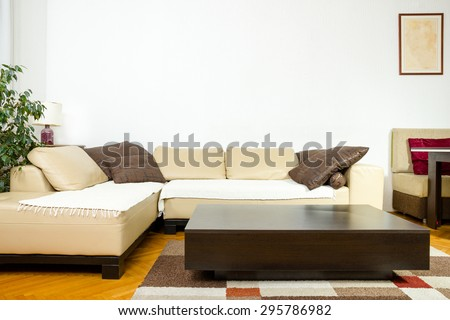 Close-up of yellow angular with pillows and low table in exclusive interior apartment. Beauty interior with corner sofa. Contemporary sitting room. Stylized living room.