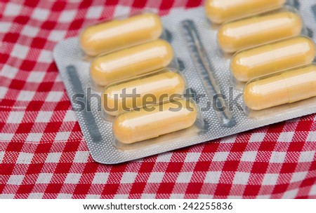 Close up of yellow capsules in blister - stock photo