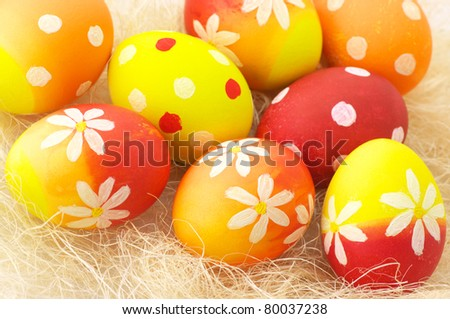 Close-up of yellow, orange and red Easter eggs in haulm. - stock photo