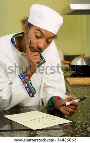 Close Up of Young African American Chef Writing Shopping List - stock photo