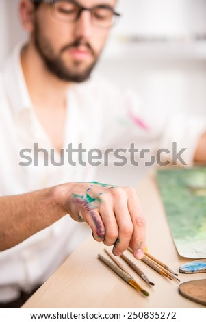 Close-up of young artist with brushes while is painting his picture. - stock photo