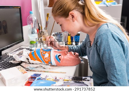 Close Up of Young Artistic Woman Carefully Painting Colorful Details onto Clay Mask at Computer Desk