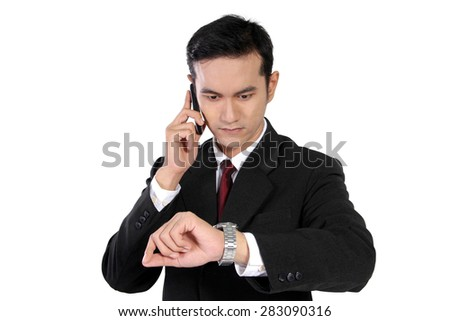 Close up of young Asian businessman looking at his watch while using cell phone, isolated on white background - stock photo