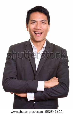 Close up of young Asian businessman with arms crossed isolated against white background