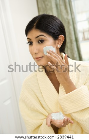Close up of young Asian/Indian woman applying facial scrub.
